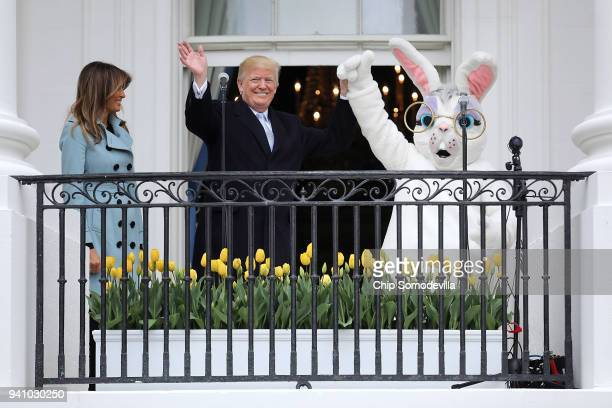 US President Donald Trump and first lady Melania Trump walk out onto the Truman Balcony with a person in an Easter Bunny costume during the 140th...