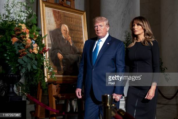 President Donald Trump and first lady Melania Trump walk past a painting of the late Supreme Court Justice John Paul Stevens after they pay their...