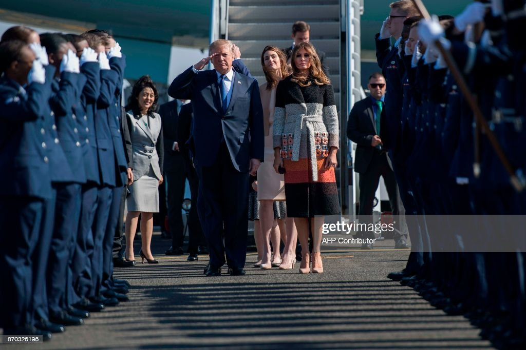 US President Donald Trump (centre L) and First Lady Melania Trump (centre R) walk through an honour cordon as they arrive at Yokota Air Base at Fussa in Tokyo on November 5, 2017. Trump touched down in Japan on November 5, kicking off the first leg of a high-stakes Asia tour set to be dominated by soaring tensions with nuclear-armed North Korea. /