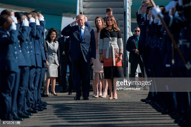 US President Donald Trump and First Lady Melania Trump walk through an honour cordon as they arrive at Yokota Air Base at Fussa in Tokyo on November...