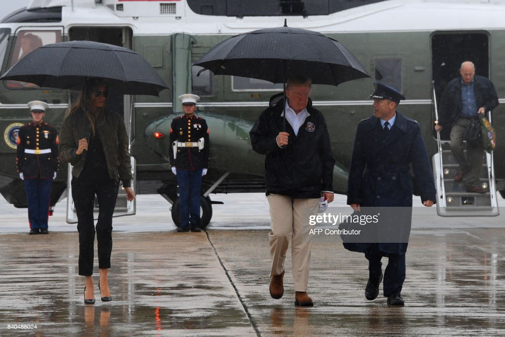 US President Donald Trump and First Lady Melania Trump walk to board Air Force One at Andrews Air Force Base, Maryland, on August 29, 2017 en route to Texas to view the damage caused by Hurricane Harvey. /