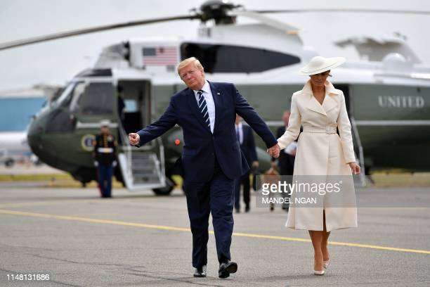 US President Donald Trump and First Lady Melania Trump walks off of Marine One to board Air Force One before departing from Southampton Airport in...