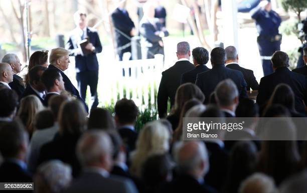 S President Donald Trump and first lady Melania Trump watch as the casket of Rev Billy Graham is carried out of the Graham's funeral service at the...
