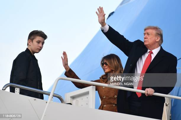 President Donald Trump and First Lady Melania Trump wave as their son Barron looks on as they make their way to board Air Force One before departing...