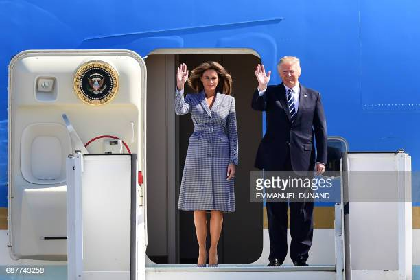 President Donald Trump and First Lady Melania Trump wave as they step off Air Force One upon their arrival at Melsbroek military airport in...