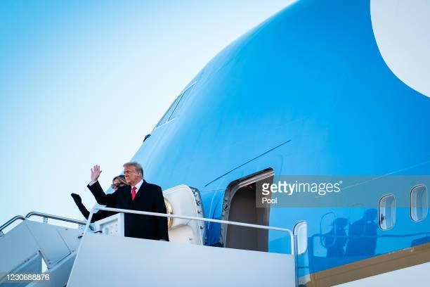 President Donald Trump and first lady Melania Trump wave to supporters as they board Air Force One to head to Florida on January 20, 2021 in Joint...
