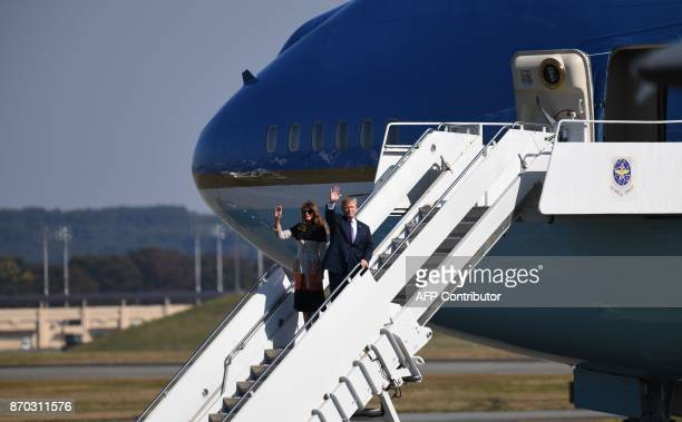 US President Donald Trump and First Lady Melania Trump wave upon arriving at US Yokota Air Base in Tokyo on November 5 2017 Trump touched down in...