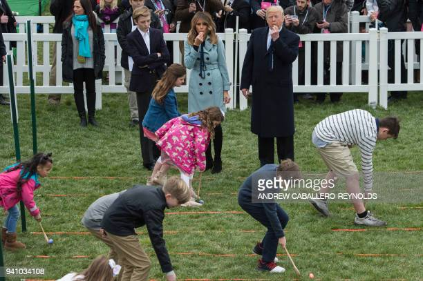 President Donald Trump and First Lady Melania Trump with son Barron blow whistles at the start of an Easter egg roll during Easter celebrations at...
