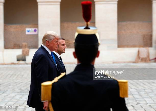 US President Donald Trump and French President Emmanuel Macron review troops during a welcome ceremony at Les Invalides in Paris on July 13 2017...