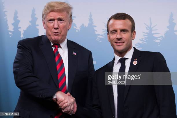 President Donald Trump and French President Emmanuel Macron shake hands before a meeting on the sidelines of the G7 Summit in La Malbaie, Quebec,...