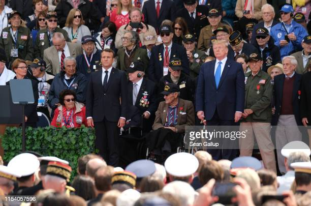 S President Donald Trump and French President Emmanuel Macron stand as American Battle of Normandy veterans and family members look on during the...