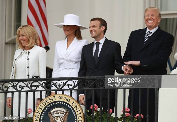 S President Donald Trump and French President Emmanuel Macron wave to invited guests from a balcony during a state arrival ceremony at the White...