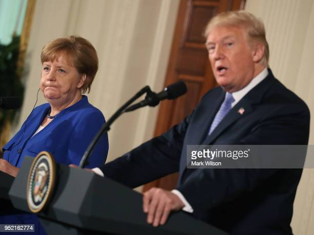 S President Donald Trump and German Chancellor Angela Merkel deliver remarks during a joint press conference after a meeting in the Oval Office at...