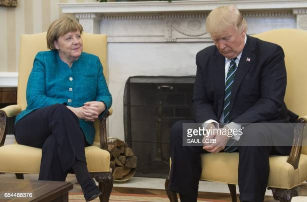President Donald Trump and German Chancellor Angela Merkel meet in the Oval Office of the White House in Washington, DC, on March 17, 2017. / AFP...