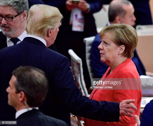 President Donald Trump and German Chancellor Angela Merkel speak together when they arrive for the first woriking session of the G20 Nations Summit...