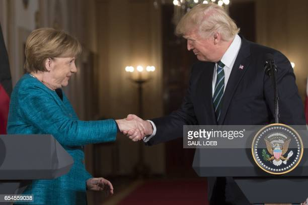US President Donald Trump and Germany's Chancellor Angela Merkel shake hands after a press conference in the East Room of the White House March 17...