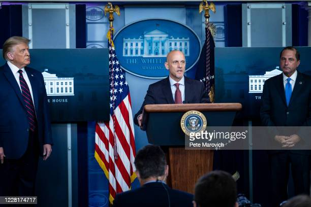 President Donald Trump and Health and Human Services Secretary, Alex Azar look on as FDA Commissioner Stephen Hahn addresses the media during a press...