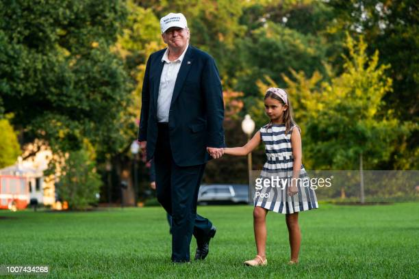 S President Donald Trump and his granddaughter Arabella Rose Kushner walk across the South Lawn as they return from a weekend stay in Bedminster New...