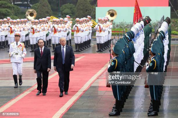 US President Donald Trump and his Vietnamese counterpart Tran Dai Quang review the honor guard at the Presidential Palace in Hanoi on November 12...