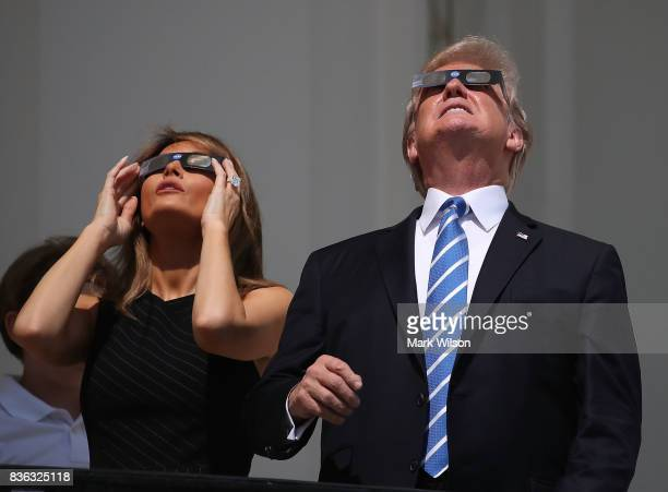 President Donald Trump and his wife first lady Melania Trump wear special glasses to view the solar eclipse at the White House on August 21, 2017 in...