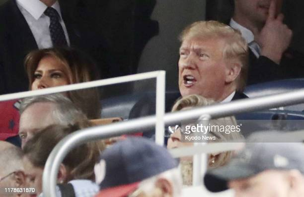US President Donald Trump and his wife first lady Melania watch Game 5 of the World Series between the Washington Nationals and Houston Astros on Oct...