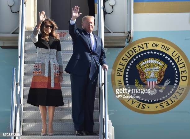 US President Donald Trump and his wife Melania wave as they arrive at Yokota Air Base at Fussa in Tokyo on November 5 2017 Trump touched down in...