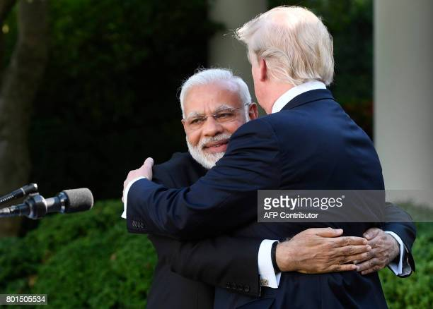 US President Donald Trump and Indian Prime Minister Narendra Modi hug after speaking to the press in the Rose Garden of the White House in Washington...