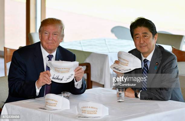 US President Donald Trump and Japanese Prime Minister Shinzo Abe pose after they signed hats reading 'Donald and Shinzo Make Alliance Even Greater'...