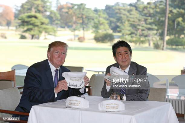 US President Donald Trump and Japanese Prime Minister Shinzo Abe poses with signed caps at Kasumigaseki Country Club on November 5 2017 in Kawagoe...