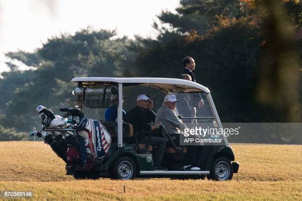 US President Donald Trump and Japanese Prime Minister Shinzo Abe return in a golf cart after playing a round of golf at the Kasumigaseki Country Club...