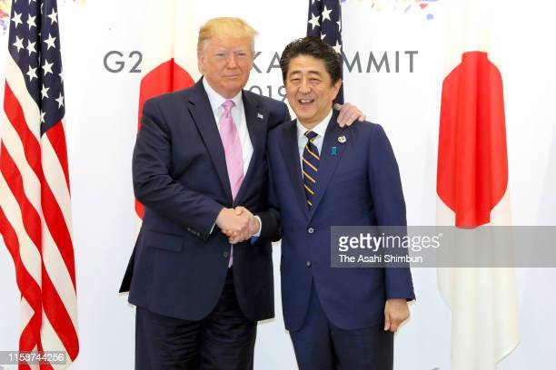 S President Donald Trump and Japanese Prime Minister Shinzo Abe shake hands prior to their bilateral meeting on the first day of the G20 summit on...