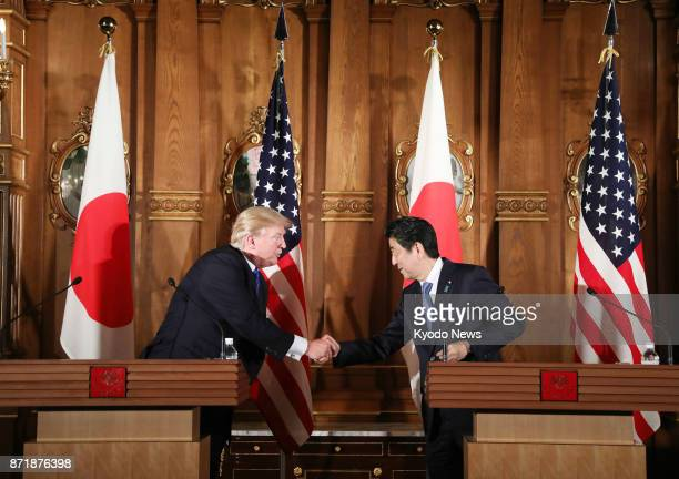 US President Donald Trump and Japanese Prime Minister Shinzo Abe shake hands during a joint press conference at the State Guest House in Tokyo on Nov...