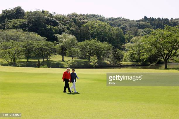 President Donald Trump and Japanese Prime Minister Shinzo Abe talk on the way to play golf at Mobara Country Club on May 26, 2019 in Chiba, Japan....