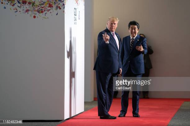 President Donald Trump and Japan's Prime Minister, Shinzo Abe, gesture towards Ivanka Trump and Jared Kushner to join them for a group photograph on...
