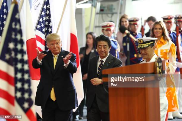 President Donald Trump and Japan's Prime Minister Shinzo Abe react before delivering a speech to Japanese and U.S. Troops as they aboard Japan...
