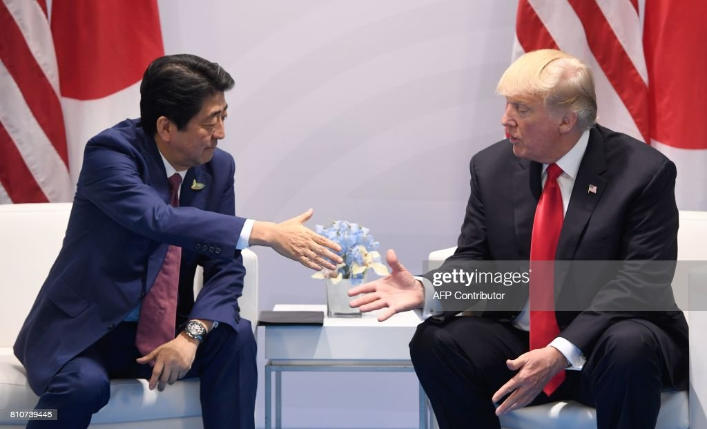 US President Donald Trump (R) and Japan's Prime Minister Shinzo Abe shake hands during a bilateral meeting on the sidelines of the G20 Summit in Hamburg, northern Germany, July 8, 2017. Leaders of the world's top economies gather from July 7 to 8, 2017 in Germany for likely the stormiest G20 summit in years, with disagreements ranging from wars to climate change and global trade. /