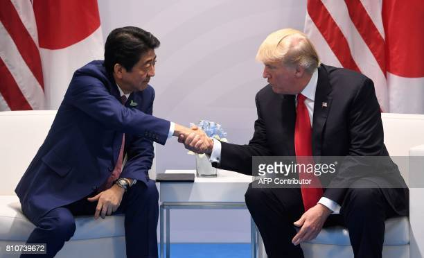 US President Donald Trump and Japan's Prime Minister Shinzo Abe shake hands during a bilateral meeting on the sidelines of the G20 Summit in Hamburg...