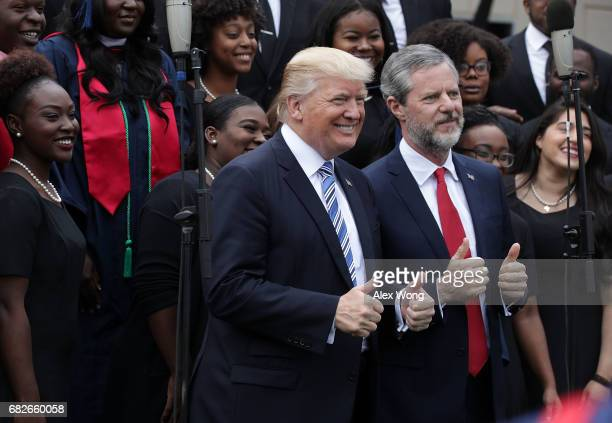 S President Donald Trump and Jerry Falwell President of Liberty University pose for photos with members of gospel choir Lu Praise during a...