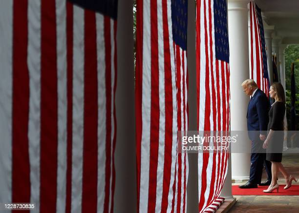President Donald Trump and Judge Amy Coney Barrett arrive at the Rose Garden of the White House in Washington, DC, on September 26, 2020. - Trump...