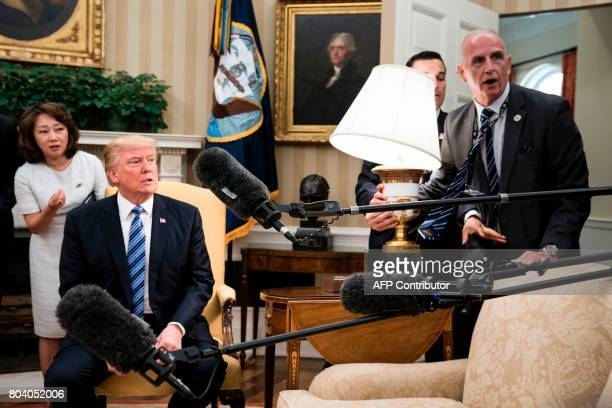 President Donald Trump and Keith Schiller react as a lamp is bumped by press before a meeting with South Korea'ss President Moon Jaein in the Oval...