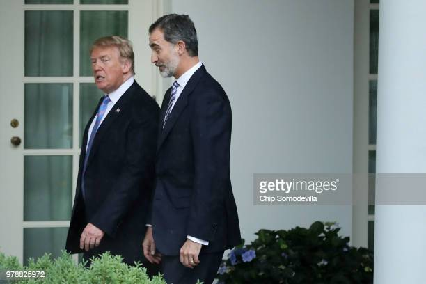 S President Donald Trump and King Felipe VI of Spain walk along the Rose Garden Colonnade before entering the Oval Office at the White House June 19...