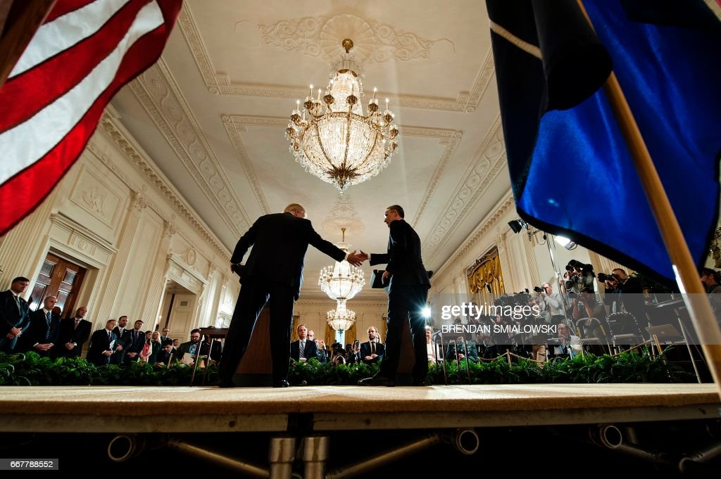 US President Donald Trump and NATO Secretary General Jens Stoltenberg (R) shake hands following a joint press conference in the East Room at the White House in Washington, DC, on April 12, 2017. / AFP PHOTO / Brendan Smialowski