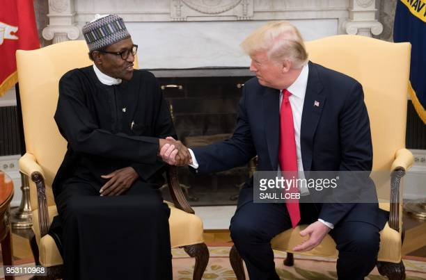 US President Donald Trump and Nigerian President Muhammadu Buhari shake hands during a meeting in the Oval Office of the White House in Washington DC...