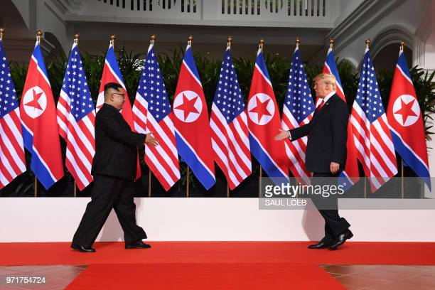 US President Donald Trump and North Korea's leader Kim Jong Un reach out to shake hands at the start of their historic USNorth Korea summit at the...