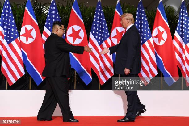 President Donald Trump and North Korea's leader Kim Jong Un reach out to shake hands at the start of their historic USNorth Korea summit at the...