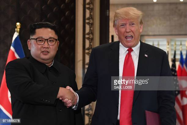 President Donald Trump and North Korea's leader Kim Jong Un shake hands following a signing ceremony during their historic US-North Korea summit, at...