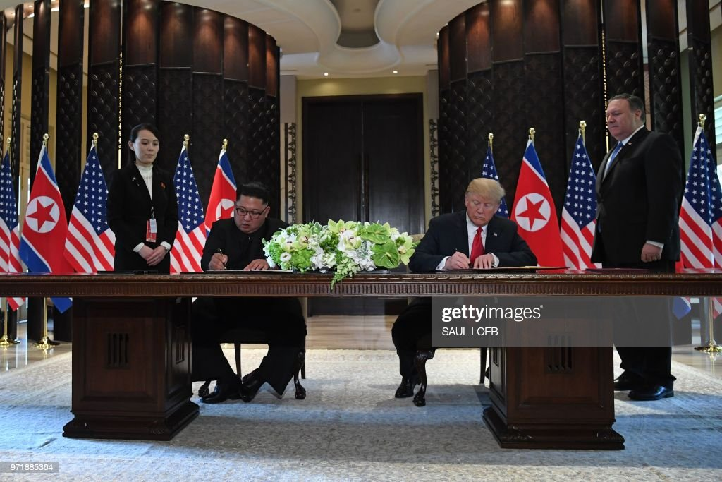 President Donald Trump (2nd R) and North Korea's leader Kim Jong Un (2nd L) sign documents as US Secretary of State Mike Pompeo (R) and the North Korean leader's sister Kim Yo Jong (L) look on at a signing ceremony during their historic US-North Korea summit, at the Capella Hotel on Sentosa island in Singapore on June 12, 2018. - Donald Trump and Kim Jong Un became on June 12 the first sitting US and North Korean leaders to meet, shake hands and negotiate to end a decades-old nuclear stand-off.