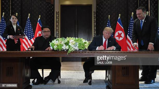 President Donald Trump and North Korea's leader Kim Jong Un sign documents as US Secretary of State Mike Pompeo and the North Korean leader's sister...