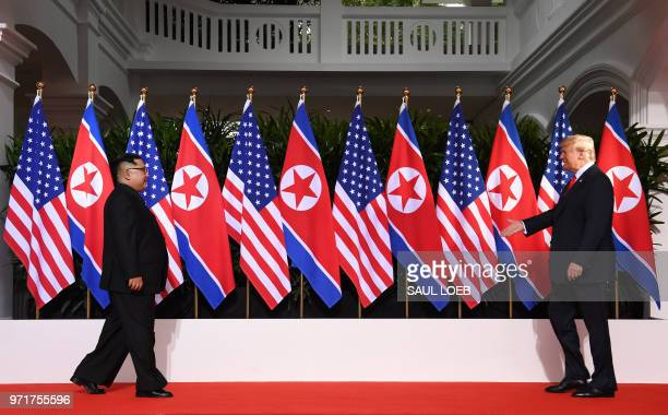 President Donald Trump and North Korea's leader Kim Jong Un walk toward one another at the start of their historic USNorth Korea summit at the...