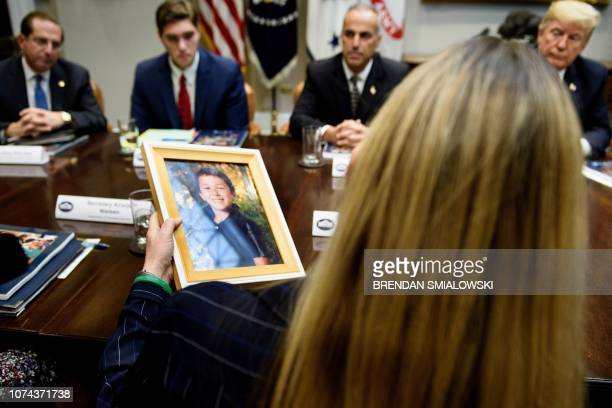 US President Donald Trump and others listen as Scarlett Lewis holding a photo of her son Sandy Hook mass shooting victim Jesse Lewis speaks during a...